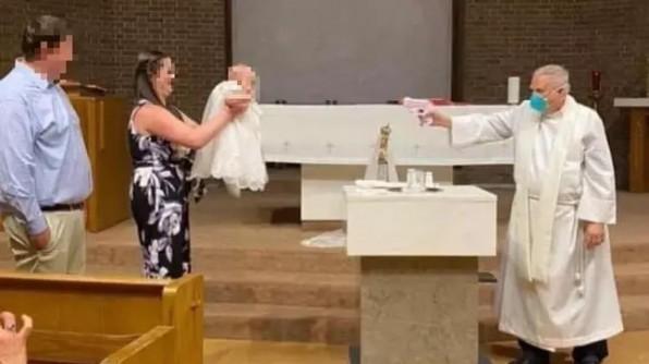 Linh mục dùng súng phun nước để rửa tội cho em bé trong mùa dịch COVID-19
